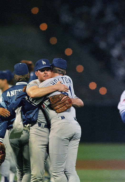 . Los Angeles Dodgers relief pitcher Jay Howell, facing camera, is hugged by teammate Brian Holton after being credited with a save in the Dodgers 4-3 win over the Oakland As in the fourth game of the World Series at Oakland Coliseum, Wednesday, Oct. 19, 1988, Oakland, Calif. The As lead the Series 3-1. (AP Photo/Rusty Kennedy)