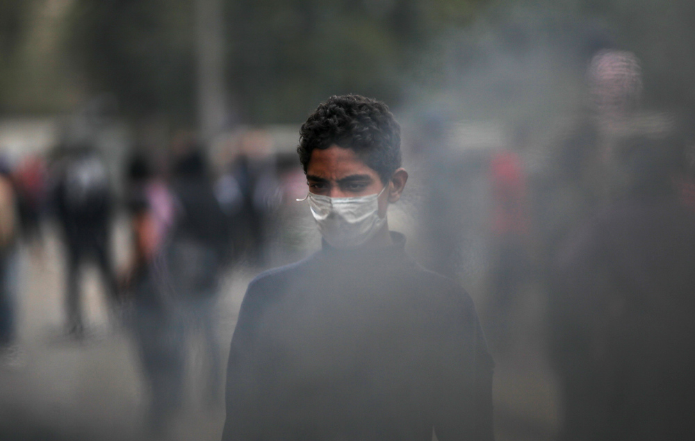 . An Egyptian protester wears a mask during clashes with riot police, not seen, near Tahrir Square, Cairo, Egypt, Monday, Jan. 28, 2013. Health and security officials say a protester has been killed in clashes between rock-throwing demonstrators and police near Tahrir Square in central Cairo. The officials say the protester died Monday on the way to the hospital after being shot. (AP Photo/Khalil Hamra)