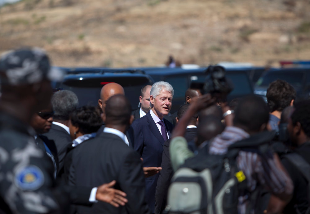 Description of . UN special envoy to Haiti and former President Bill Clinton, center, arrives for a memorial service for victims of the 2010 earthquake, at Titanyen, a mass burial site north of Port-au-Prince, Haiti, Saturday, Jan. 12, 2013. Haitians recalled the tens of thousands of people who lost their lives in a devastating earthquake three years ago, marking the disaster\'s anniversary Saturday with a simple ceremony. Haiti\'s previous presidential administration said 316,000 people were killed but no one really knows how many died.  (AP Photo/Dieu Nalio Chery)
