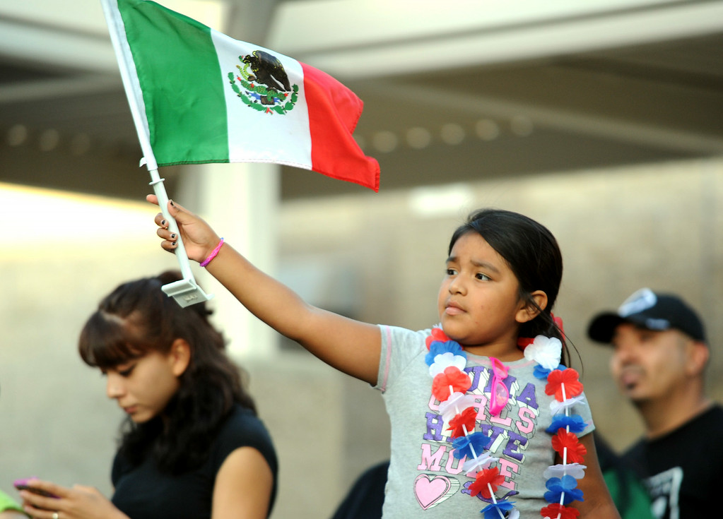 . Emily De Los Angeles, 6, of Boyle Heights, waves a mexican flag during a town hall meeting on Wednesday, July 2, 2014 at Murrieta Mesa High School in Murrieta, Ca. The meeting is being held in response to immigrants who were being processed through a Texas Border Patrol Station and delivered to the Murrieta Border Patrol Station on Tuesday, which created protests from both sides of the immigration issue. (Micah Escamilla/The Sun)