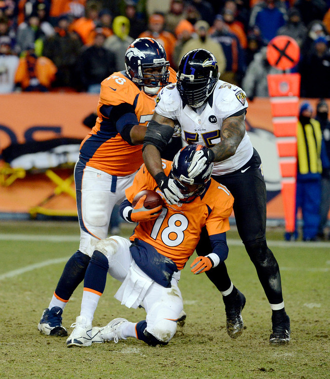 . Denver Broncos quarterback Peyton Manning (18) gets sacked by Baltimore Ravens outside linebacker Terrell Suggs (55) during the fourth quarter.  The Denver Broncos vs Baltimore Ravens AFC Divisional playoff game at Sports Authority Field Saturday January 12, 2013. (Photo by Tim Rasmussen/The Denver Post)