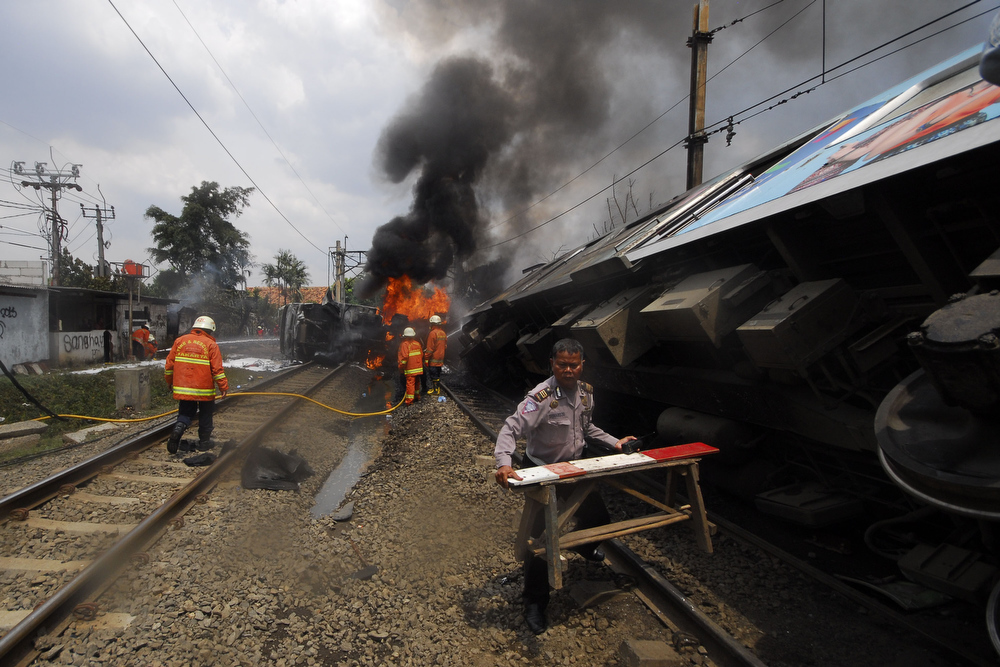 . Emergency crews tackle the fire on the train wreck on December 9, 2013 on the outskirts Jakarta, Indonesia. A commuter train collided with a vehicle reportedly carrying liquefied gas canisters at around 11:20am local time. At least five people are reported dead.  (Photo by Nurcholis Anhari Lubis/Getty Images)