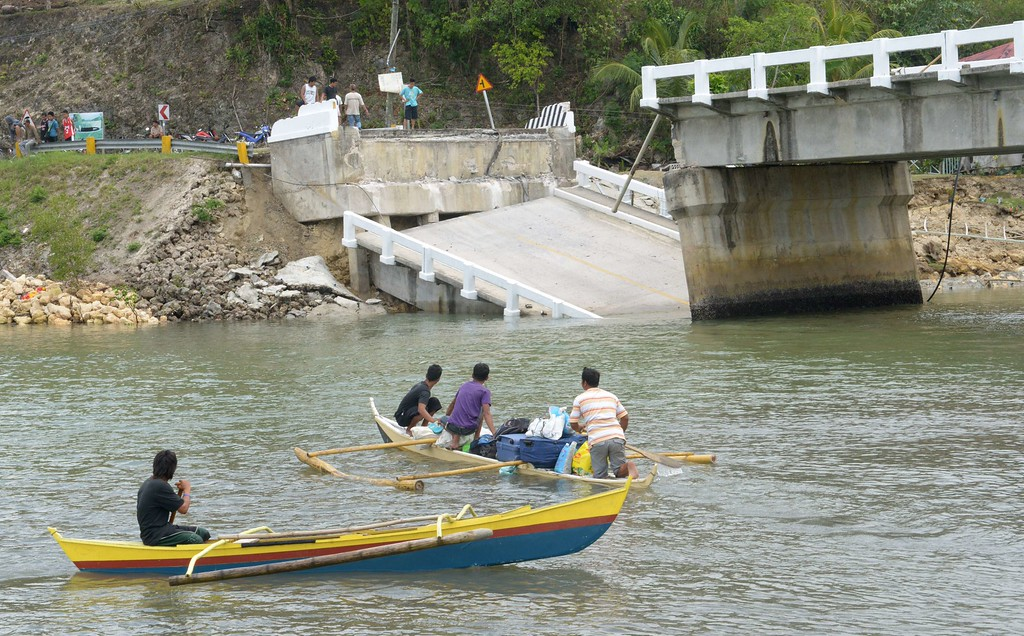 . Residents use an outrigger to cross a river near a damaged bridge on the popular tourist island of Bohol, central Philippines on October 16, 2013 following a 7.1-magnitude earthquake in the area on October 15.  AFP PHOTO / Jay DIRECTO/AFP/Getty Images