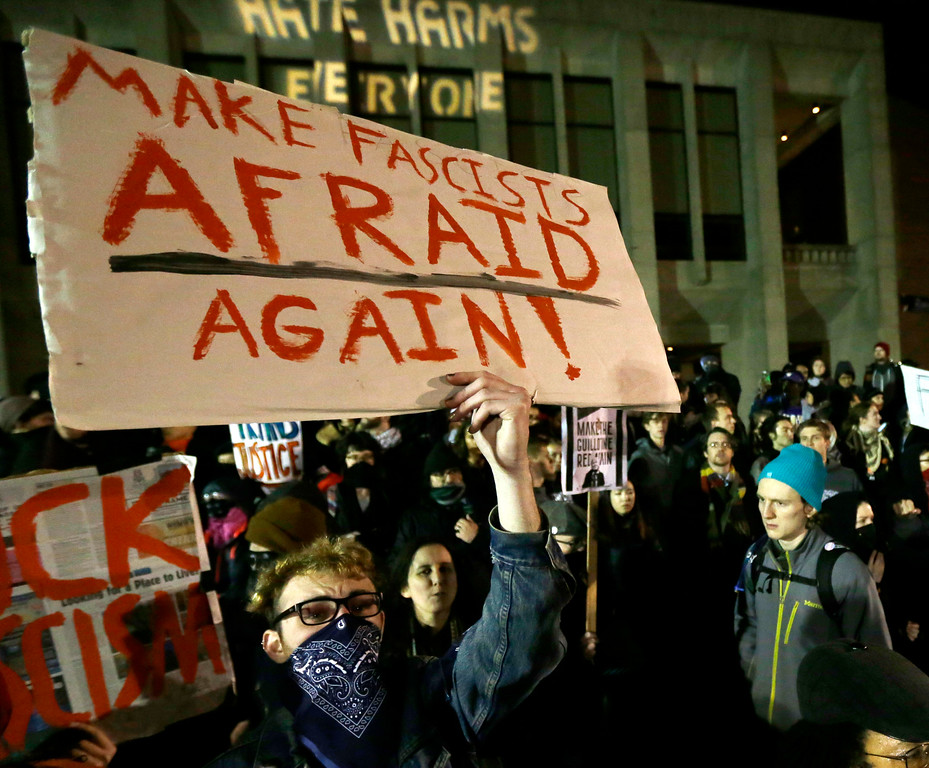 ". A protester holds a sign that reads ""Make Fascists Afraid Again!\"" during a demonstration in front of Kane Hall on the University of Washington campus where far-right commentator Milo Yiannopoulos was giving a speech, Friday, Jan. 20, 2017, in Seattle. (AP Photo/Ted S. Warren)"