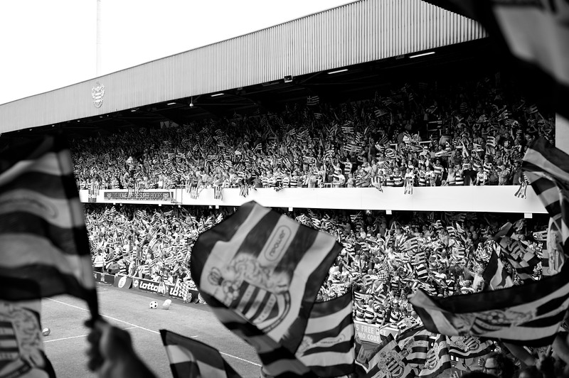 Queens Park Rangers fans celebrating promotion to the English Premier League after a fifteen year absence from the top flight.<br /> <br /> The club laid on flags for every supporter and they whirled them around like crazy before kick-off.<br /> <br /> Nikon D700 + 70-200mm 2.8 VRII