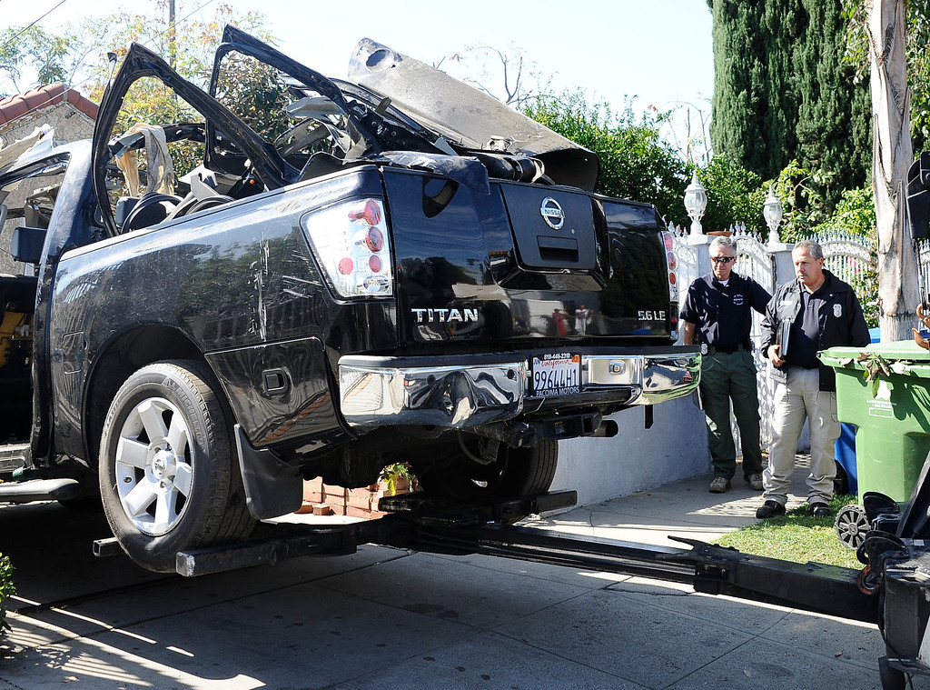 . LAPD and LAFD investigators watch as the pickup truck with propane tanks inside is towed away after a explosion rocked a North Hollywood neighborhood early Tuesday.  The blast happened in the 11000 block of Miranda Street around 12:30 a.m. Several 911 calls were received about some sort of explosion. Officials have determined the explosion happened inside the pickup truck.  When first responders arrived at the scene, they found the truck parked in a rear yard. When they got closer, they saw at least one propane tank inside the vehicle and backed off. North Hollywood CA. Oct 22,2013.  Photos by Gene Blevins/LA Daily News
