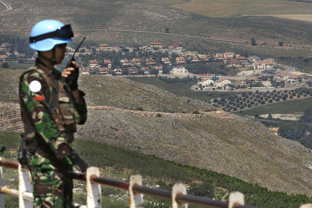. An Indonesian U.N peacekeeper patrols the Lebanese side of the Lebanese-Israeli border in the southern village of Kfar Kila, Lebanon, Tuesday May 7, 2013. President Bashar Assad\'s regime has given a Palestinian militant group the go-ahead to set up missiles to attack Israel in the wake of recent Israeli airstrikes on the Syrian capital, a spokesman for the group said Tuesday. Israel\'s government has not formally confirmed involvement in the strikes on Syria. However, Israeli officials have said the attacks were meant to prevent advanced Iranian weapons from reaching Lebanon\'s Hezbollah militia, an ally of Syria and foe of Israel. The Israeli settlement of Metulla, is seen at background. (AP Photo/Hussein Malla)