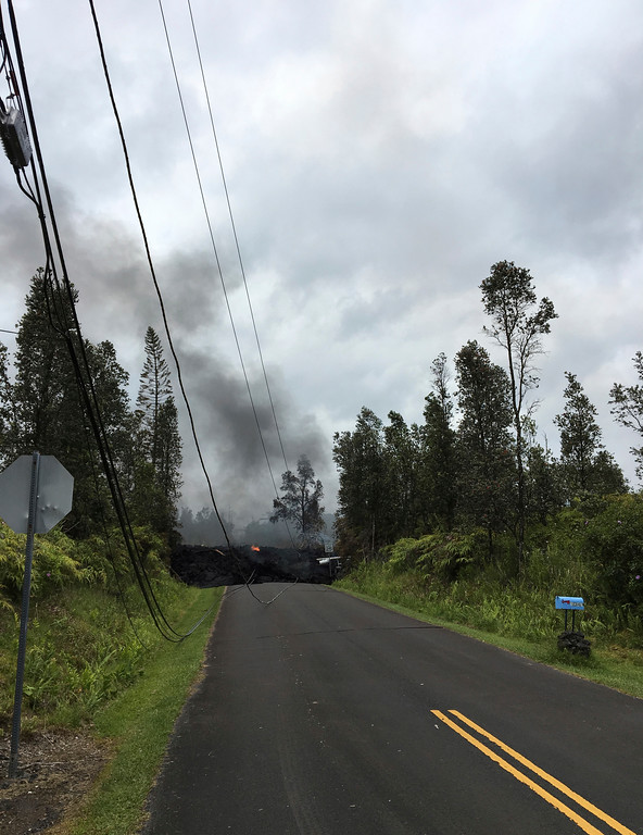. Fallen cable lines are seen on the road as lava burns in Leilani Estates in Pahoa, Hawaii, Saturday, May 5, 2018. Hundreds of anxious residents on the Big Island of Hawaii hunkered down Saturday for what could be weeks or months of upheaval as the dangers from an erupting Kilauea volcano continued to grow. (AP Photo/Marco Garcia)