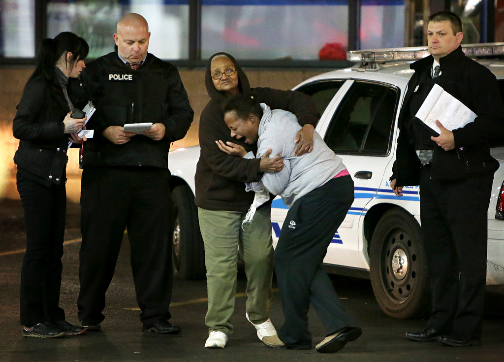 . Toni Martin, front center, cries out on Wednesday, Dec. 24, 2014, as she talks to police at the scene where she says her son was fatally shot Tuesday at a gas station in Berkeley, Mo. Authorities did not immediately identify the man who was shot. But the St. Louis Post-Dispatch reported that Toni Martin, said he was her son, Antonio Martin. (AP Photo/St. Louis Post-Dispatch, David Carson)