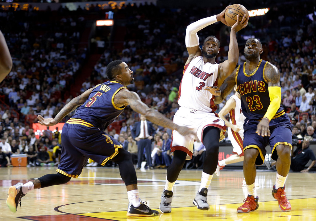 . Miami Heat\'s Dwyane Wade (3) looks to pass as Cleveland Cavaliers\' J.R. Smith (5) and LeBron James (23) defend during the first half of an NBA basketball game, Monday, March 16, 2015, in Miami. (AP Photo/Lynne Sladky)