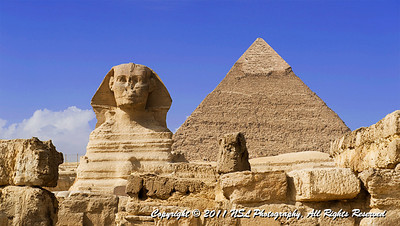 The Great Sphinx of Giza in the foreground with the Pyramid of Khafre in the background at the Giza Necropololis. Note the prominent display of casing stones at the apex of the Pyramid of Khafre.