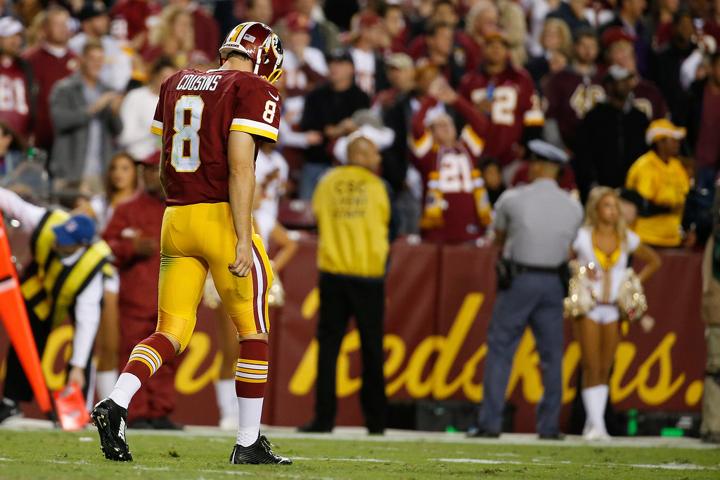 . Washington Redskins quarterback Kirk Cousins walks off the field after an interception during the second half of an NFL football game against the New York Giants in Landover, Md., Thursday, Sept. 25, 2014. (AP Photo/Alex Brandon)
