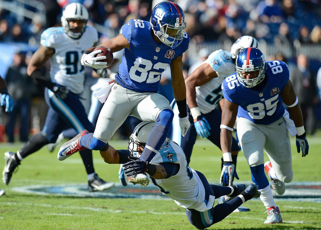 . New York Giants wide receiver Rueben Randle (82) leaps past Tennessee Titans safety George Wilson (21) in the first half of an NFL football game Sunday, Dec. 7, 2014, in Nashville, Tenn. (AP Photo/Mark Zaleski)