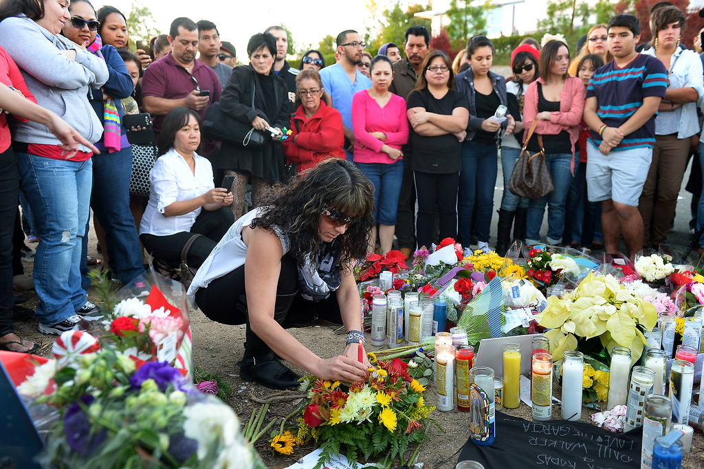 . Daly Manning places a candle at a memorial for Paul Walker and Roger Rodas, Sunday, December 1, 2013, at the scene of their fatal crash site on Hercules Street near Kelly Johnson Parkway in Valencia. (Photo by Michael Owen Baker/L.A. Daily News)