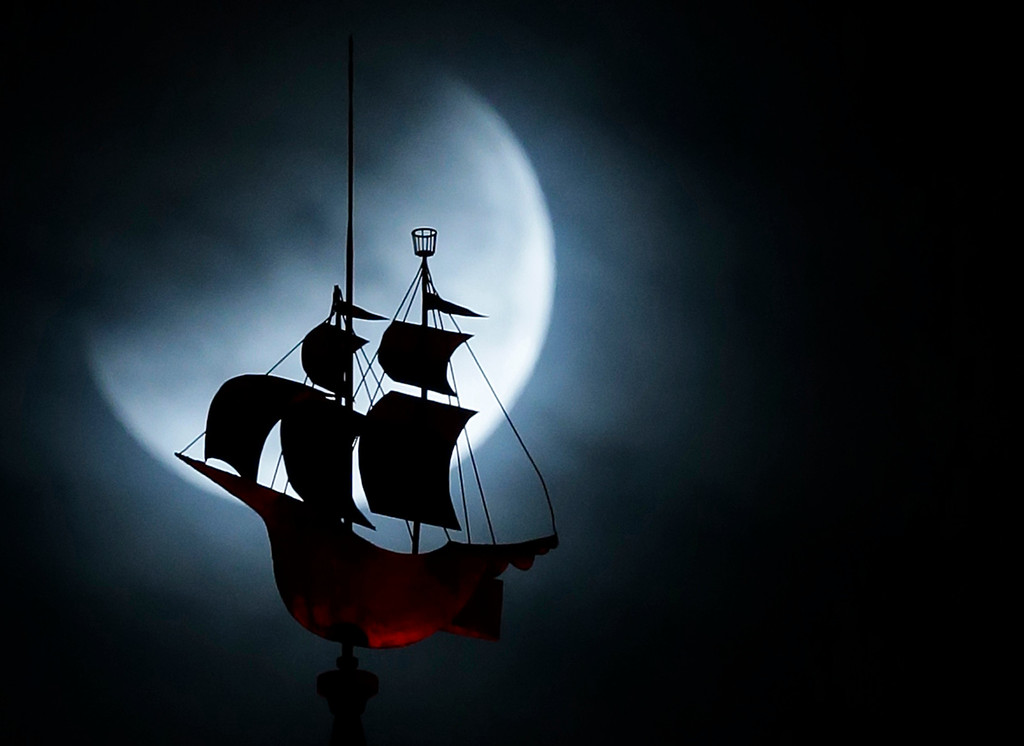 . The Earth\'s shadow begins to fall on the moon during a total lunar eclipse, as it goes behind a weathervane shaped like a Spanish galleon on the Freedom Tower, Wednesday, Oct. 8, 2014 in Miami. (AP Photo/Wilfredo Lee)
