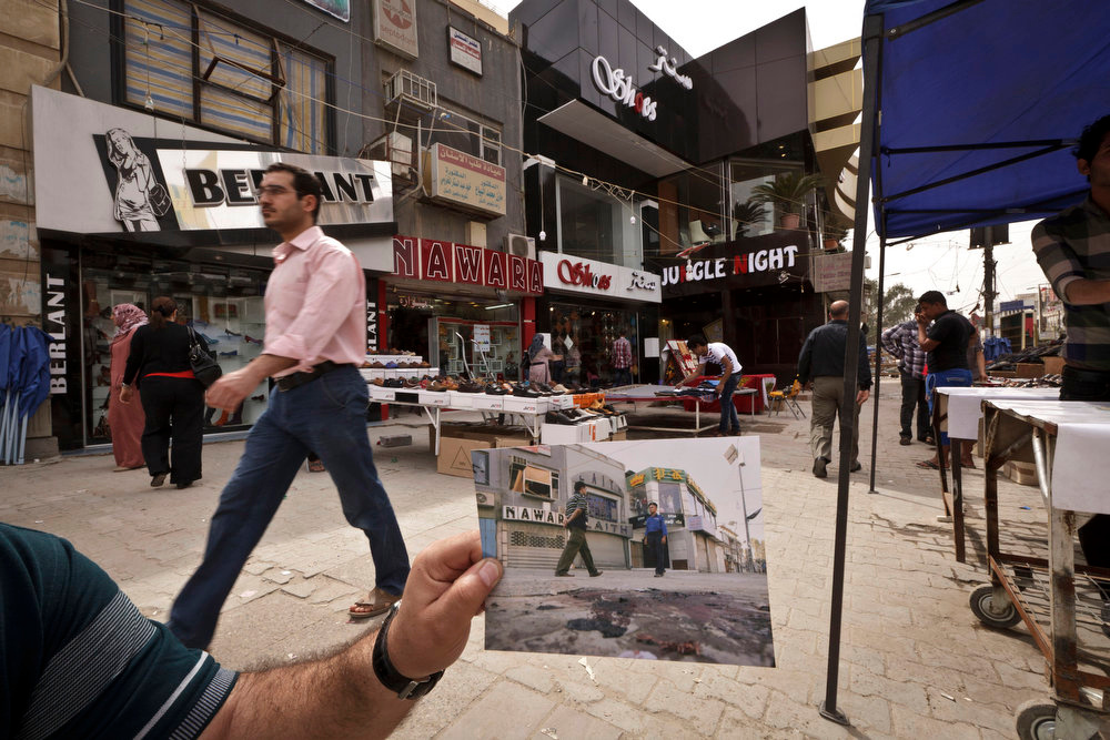 . Shoppers walk in Baghdad\'s busy shopping district of Karrada, at the same site of a photo taken by Associated Press photographer Hadi Mizban on Monday, Sept. 29, 2008 after a bombing that killed 22 people. Bloody attacks launched by terrorists who thrived in the post-invasion chaos are painfully still frequent, albeit less so than a few years back, and sectarian and ethnic rivalries are again tearing at the fabric of national unity. Photo taken on March 16, 2013. (AP Photo/Maya Alleruzzo)