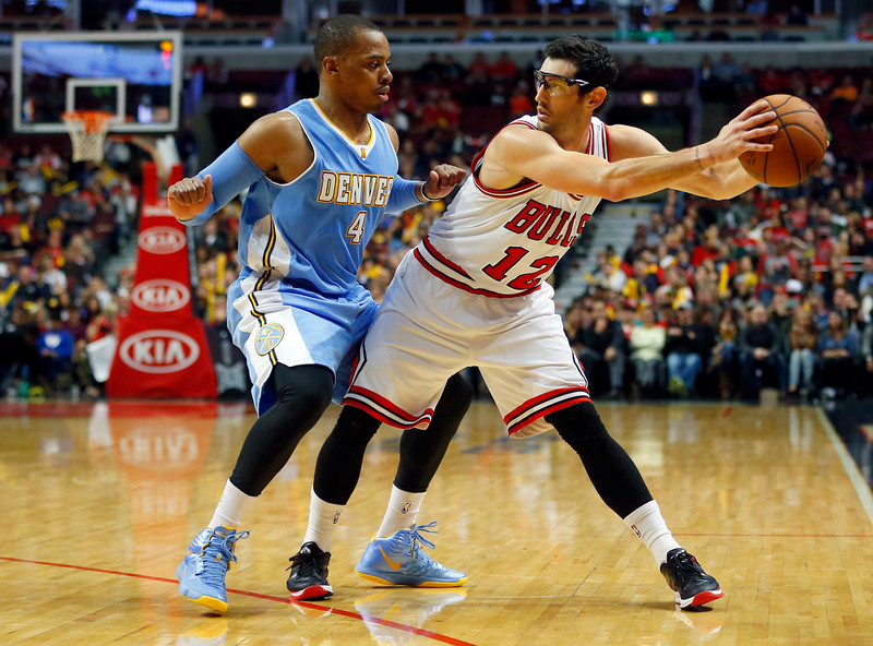 . Chicago Bulls guard Kirk Hinrich (12) holds the ball away from Denver Nuggets guard Randy Foye (4) during the second half of a pre-season NBA basketball game in Chicago, on Monday Oct. 13, 2014. The Bulls won the game 110-90. (AP Photo/Jeff Haynes)