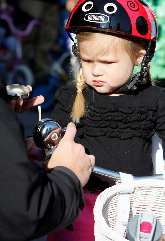 . Chloe Mead, 3, of Redlands, watches her father, Chris, fixes her bell prior to the public race portion of the Redlands Bicycle Classic on Saturday, April 5, 2014 in Redlands, Ca. (Photo by Micah Escamilla for the Redlands Daily Facts)