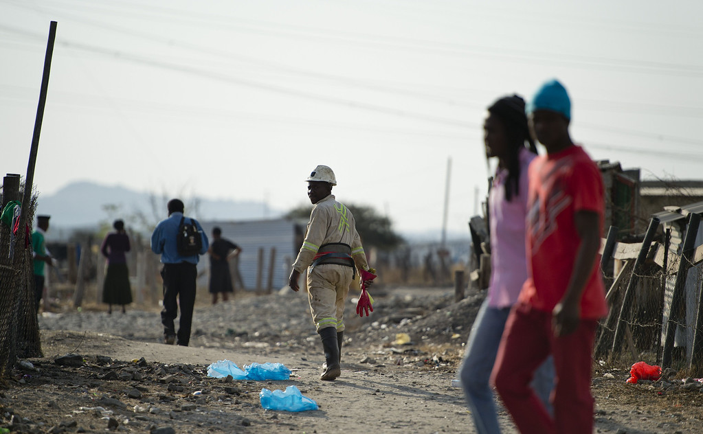 . A miner (C) makes his way home after work on July 9, 2013 in the Nkaneng shantytown next to the platinum mine, run by British company Lonmin, in Marikana. On August 16, 2012, police at the Marikana mine open fire on striking workers, killing 34 and injuring 78, during a strike was for better wages and living conditions. Miners still live in dire conditions despite a small wage increase.  ODD ANDERSEN/AFP/Getty Images