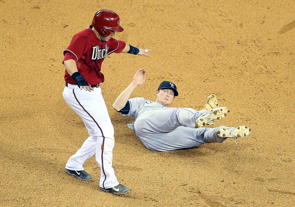 . Infielder DJ LeMahieu #9 of the Colorado Rockies falls to the ground after a collision with Miguel Montero #26 of the Arizona Diamondbacks as he broke up a double play during the sixth inning of the MLB game at Chase Field on April 30, 2014 in Phoenix, Arizona.  (Photo by Christian Petersen/Getty Images)