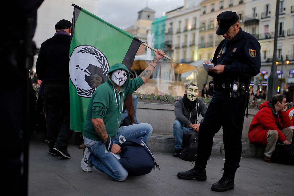 . A Spanish activist wearing a mask performs holding a flag as police stop and identify him during a protest against corrupt governments and corporations, in support of the anonymous activist movement, at the Sol square, in Madrid, Spain, Tuesday, Nov 5, 2013, as part of a Million Mask March of similar rallies around the world. (AP Photo/Andres Kudacki)