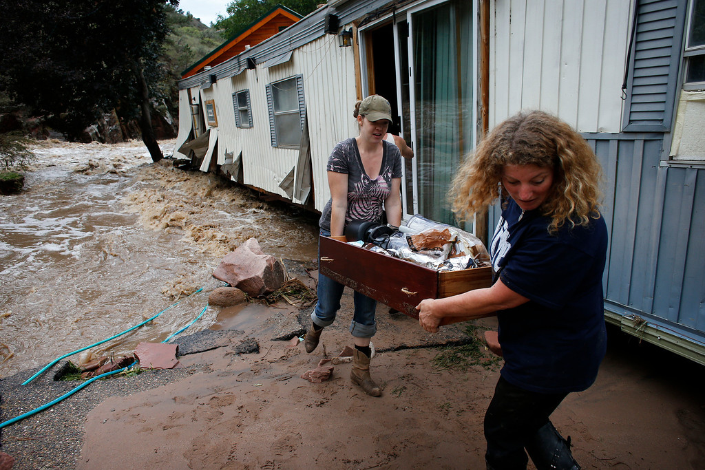 . Water rushes through a destroyed home as  resident Holly Rob, center, and her neighbor and friend Pam Bowers salvage belongings after floods left their town\'s homes and infrastructure in a shambles Lyons, Colo., Friday Sept. 13, 2013. (AP Photo/Brennan Linsley)