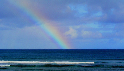 Rainbow into the ocean Sunset Point  North Shore Oahu, Hawaii