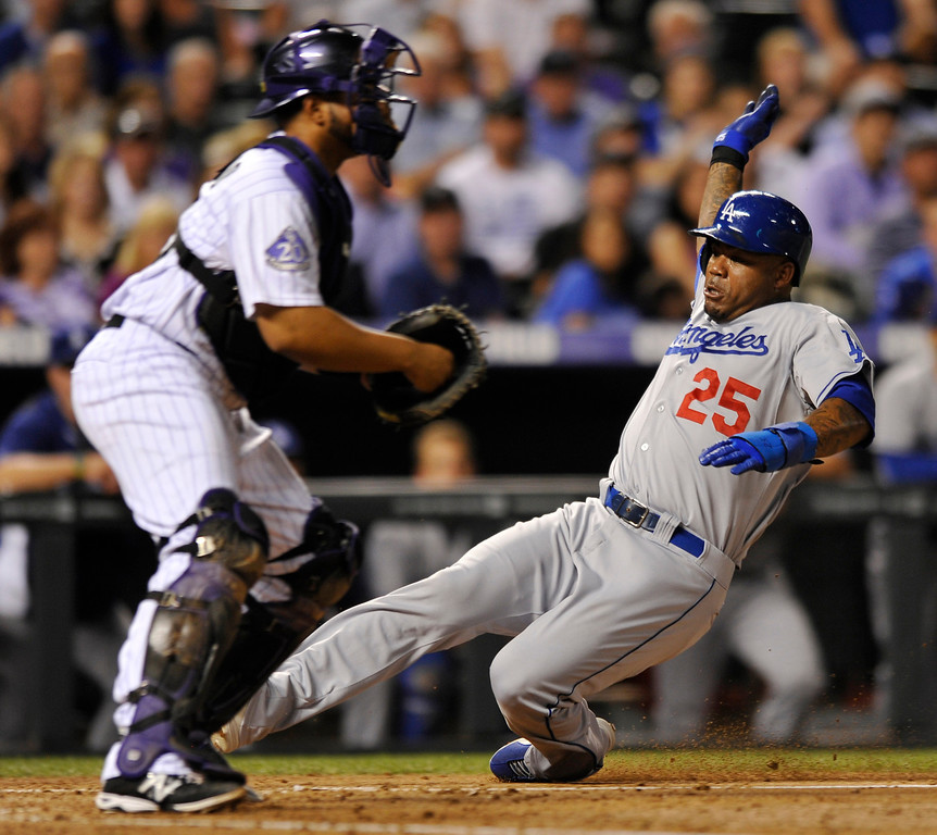 . Los Angeles Dodgers\' Carl Crawford (25) scores on a sacrifice fly by Adrian Gonzalez as Colorado Rockies catcher Wilin Rosario (20) waits for the late throw in the fifth inning of a baseball game, Tuesday, Sept. 3, 2013, in Denver. (AP Photo/Jack Dempsey)