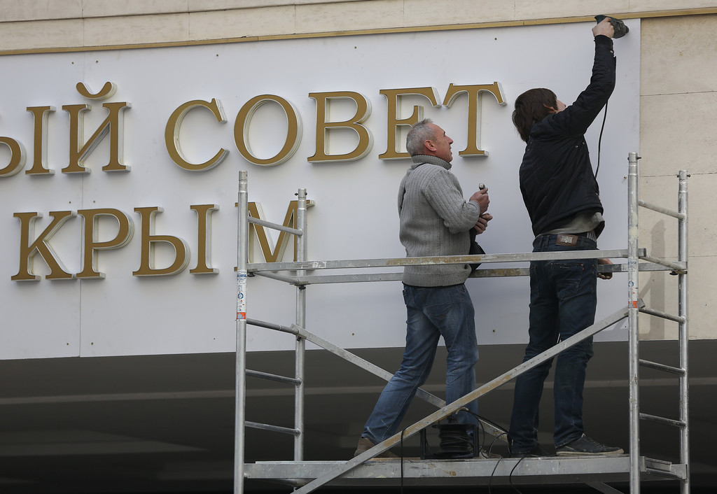 ". Workers install new sign on a local parliament building reading ""State council of Crimean Republic\"", in Simferopol, Crimea, on Wednesday, March 19, 2014. Russian parliament is expected to approve Crimean appeal to join the Russian Federation on Thursday.(AP Photo/Max Vetrov)"