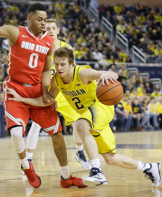. Michigan guard Spike Albrecht (2) drives against Ohio State guard D\'Angelo Russell (0) during the first half of an NCAA college basketball game, Sunday, Feb. 22, 2015 in Ann Arbor, Mich. (AP Photo/Carlos Osorio)