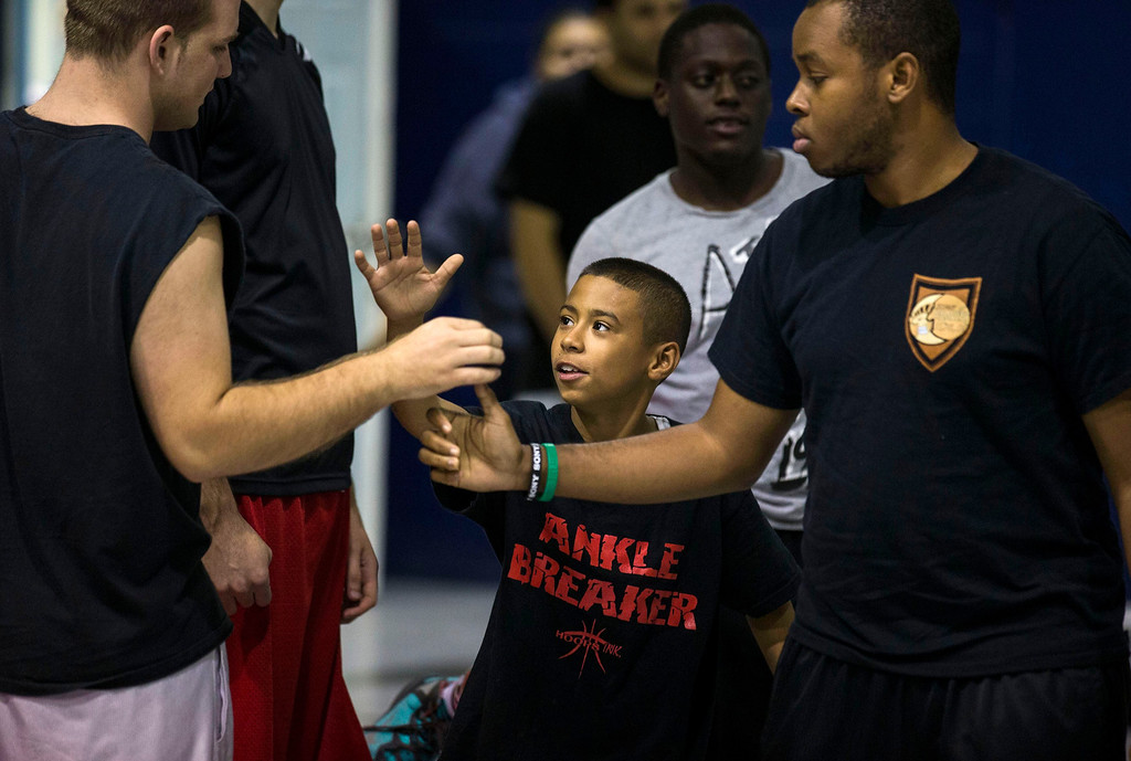 . Downey Christian high school varsity basketball player 11-year-old Julian Newman (C) greets other participants during Friday evening pickup basketball games at Downey Christian School in Orlando, Florida February 22, 2013. At 4 feet 5 inches tall, starting point guard Julian Newman stands waist high next to other players on his Florida high school basketball team. But his talent towers over the competition. At only 11, Newman leads the state of Florida in assists per game this season and ranks fifth nationally, according to Maxpreps.com, which maintains statistics on high school sports.  REUTERS/Scott Audette