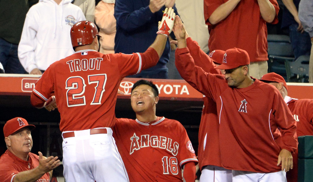 . Los Angeles Angels\' Mike Trout (27) high fives teammates after scoring on a single by Albert Pujols (not pictured) in the eighth inning of a baseball game against the New York Yankees at Anaheim Stadium in Anaheim, Calif., on Tuesday, May 6, 2014.  (Keith Birmingham Pasadena Star-News)
