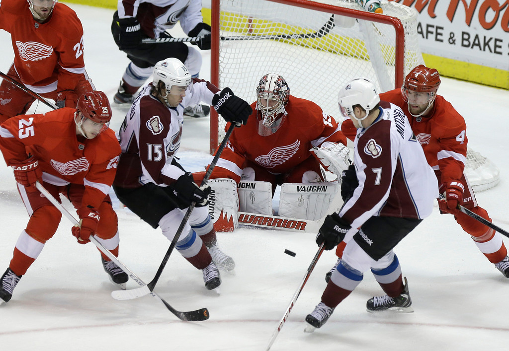 . Detroit Red Wings center Cory Emmerton (25) and defenseman Jakub Kindl (4), of the Czech Republic, defend Colorado Avalanche right wing P.A. Parenteau (15) and center John Mitchell (7) in front of Detroit goalie Jimmy Howard (35) during the third period of an NHL hockey game in Detroit, Tuesday, March 5, 2013. Detroit won 2-1. (AP Photo/Carlos Osorio)