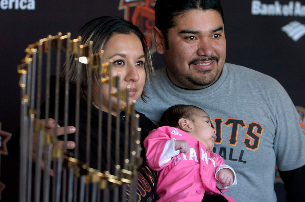 . Rigo and Ericka Gonzales, of Richmond, hold two-month-old daughter Isabel as they pose with the World Series Trophy as it makes a stop at the Richmond Memorial Auditorium in Richmond, Calif. on Monday, Jan. 14, 2013.  (Kristopher Skinner/Staff)