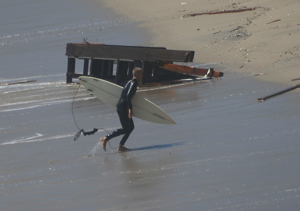 . Aug 28,2014, Malibu CA. A surfer goes by the front sun deck that was rip apart from the Pt. Mugu LA county lifeguard station that was destroyed from the big waves Thursday. The station that was used in the 1990\'s TV series Baywatch was undermined  by the big waves from Hurricane Marie Wednesday night.  The LA county lifeguard building as been there for over 30+yrs and today it was slowly torn apart by todays big waves along PCH.  Photo by Gene Blevins/LA Daily News