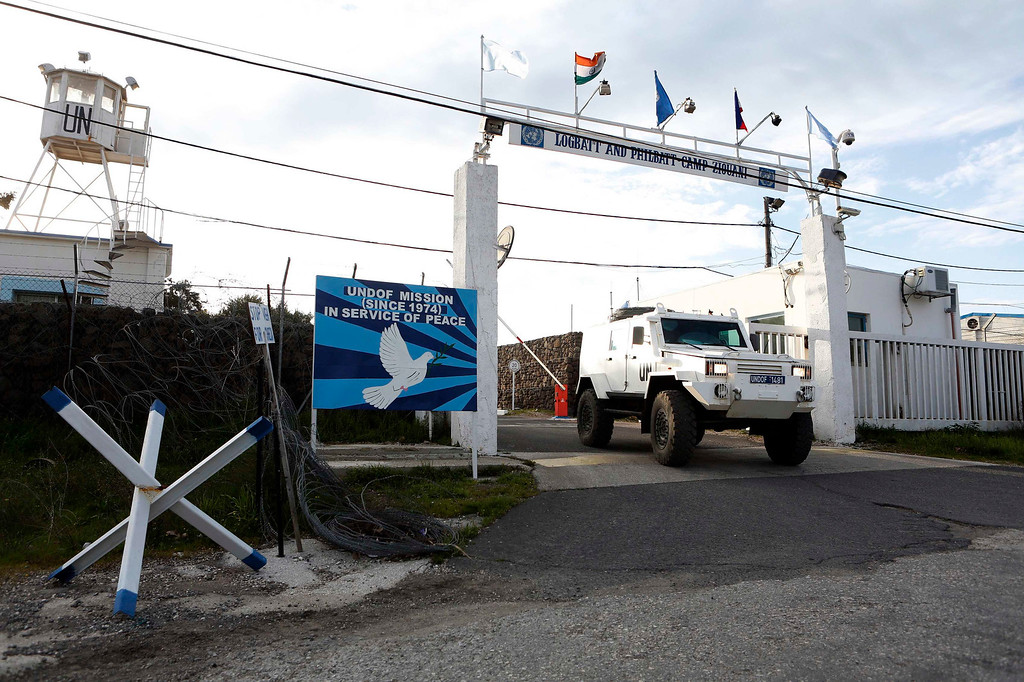 . A United Nations armoured car drives through a gate at a U.N. base near the Kuneitra border crossing between Israel and Syria, in the Israeli occupied Golan Heights March 8, 2013. Israel voiced confidence on Thursday that the United Nations could secure the release of U.N. peacekeepers seized by Syrian rebels near the Golan Heights on Wednesday, signalling it would not intervene in the crisis. Israel captured the Golan Heights in the 1967 Middle East war and annexed it in 1981 in a move not recognized internationally. REUTERS/Baz Ratner