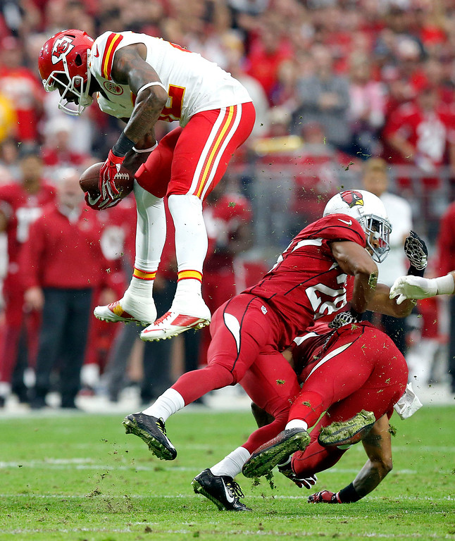 . Kansas City Chiefs wide receiver Dwayne Bowe, left, leaps over Arizona Cardinals free safety Rashad Johnson, right, and Justin Bethel, center, during the first half of an NFL football game, Sunday, Dec. 7, 2014, in Glendale, Ariz. (AP Photo/Ross D. Franklin)