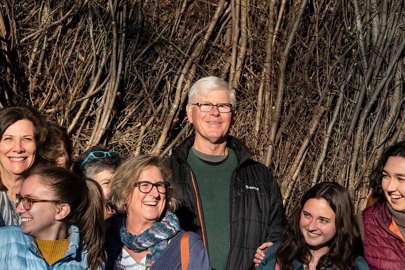 """A large crowd gathered on the Davidson campus Friday afternoon to celebrate the conclusion of a piece of """"stickwork"""" art by North Carolina artist Patrick Dougherty and his son, Sam. The construction of the work required three weeks of work in sometimes abysmal weather, and helping hands from a large number of volunteers. Dougherty stood at the center of a group photo taken at the event."""