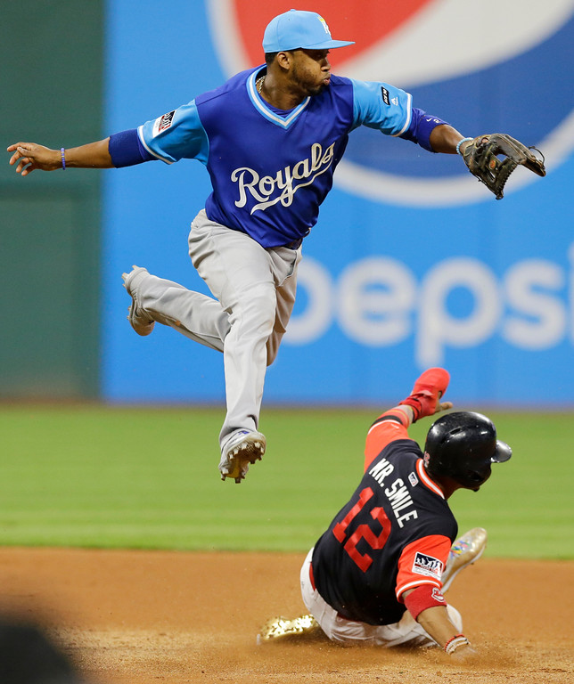 . Cleveland Indians\' Francisco Lindor slides safely into second base as Kansas City Royals\' Alcides Escobar watches the ball go past him during the seventh inning of a baseball game, Friday, Aug. 25, 2017, in Cleveland. Lindor advanced to third base on a throwing error by Royals catcher Salvador Perez. (AP Photo/Tony Dejak)