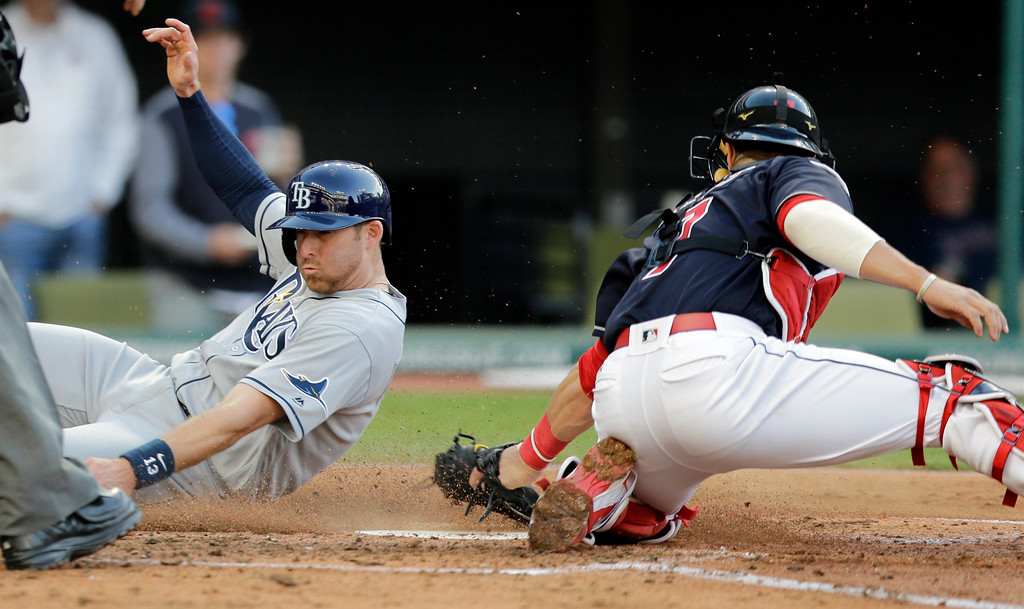 . Tampa Bay Rays\' Brad Miller scores against Cleveland Indians catcher Yan Gomes in the third inning of a baseball game, Monday, May 15, 2017, in Cleveland. Miller scored on a sacrifice fly by Steven Souza Jr. (AP Photo/Tony Dejak)