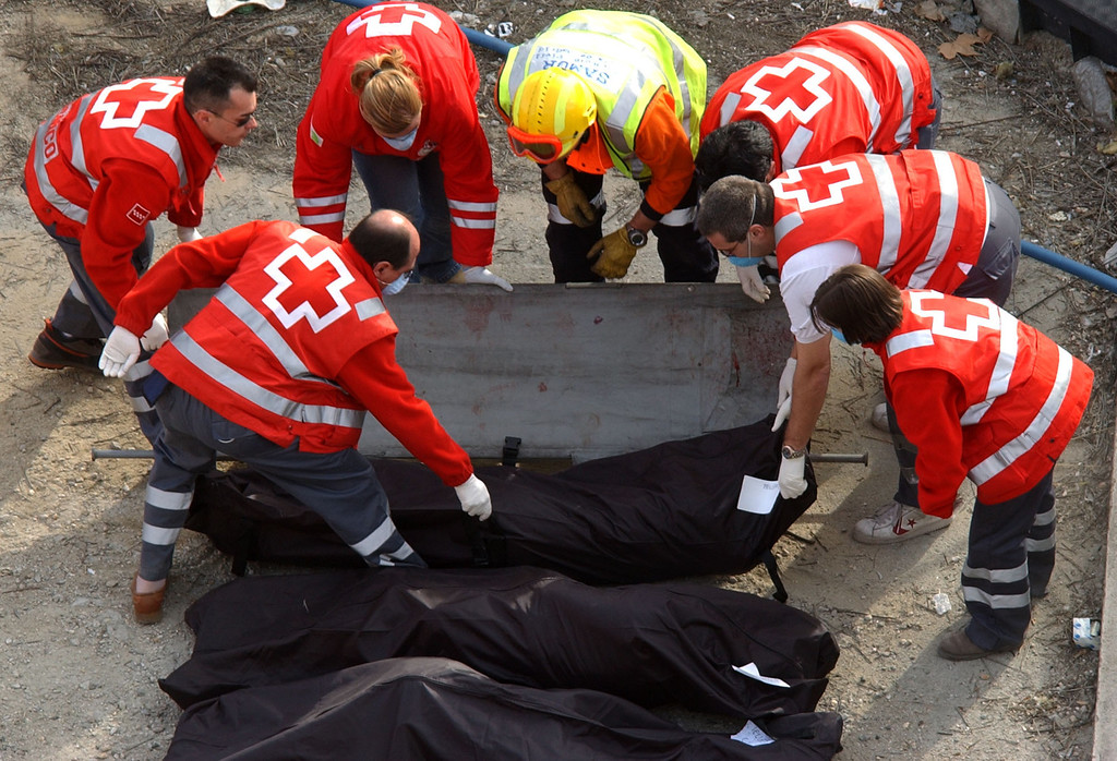 . Rescue workers remove victims at the Atocha train station following a blast there,  after explosions rocked three  train stations  in Madrid Thursday, March 11, 2004,  just three days before Spain\'s general elections. The blasts killed more than 173 rush-hour commuters and wounded more than 500 in Spain\'s worst terrorist attack ever. (AP Photo/Peter Dejong)