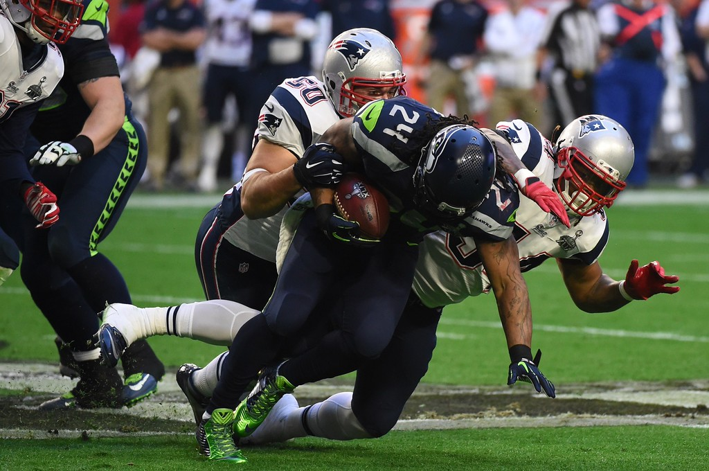 . Marshawn Lynch (C) of the Seattle Seahawks is tackled by Rob Ninkovich (L) and  Dont\'a Hightower (R) of the New England Patriots during Super Bowl XLIX on February 1, 2015 at the University of Phoenix Stadium in Glendale, Arizona.        AFP PHOTO /  TIMOTHY  A. CLARYTIMOTHY A. CLARY/AFP/Getty Images
