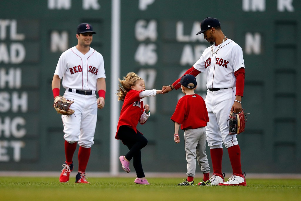 . Young cancer patients interact with Boston Red Sox\'s Andrew Benintendi, left, and Mookie Betts right, as they take the field for the national anthem before a baseball game against the Cleveland Indians in Boston, Tuesday, Aug. 21, 2018. (AP Photo/Michael Dwyer)