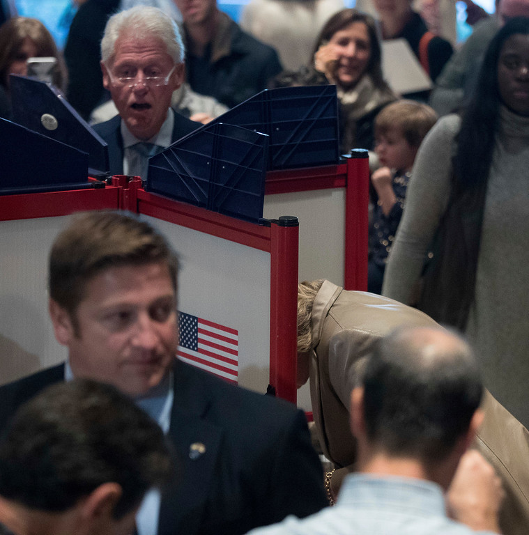 . Democratic presidential candidate Hillary Clinton, bottom right, accompanied by her husband, former President Bill Clinton, top left, votes at Douglas G. Grafflin School in Chappaqua, N.Y., Tuesday, Nov. 8, 2016. (AP Photo/Andrew Harnik)