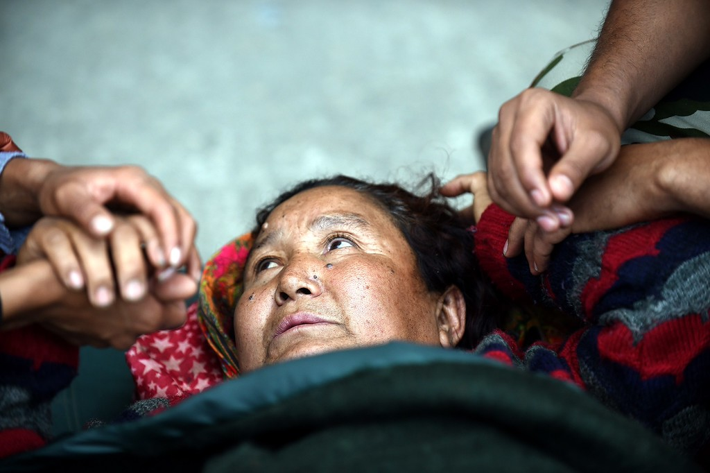 . An injured Nepalese woman looks on at a field hospital at an airport in Kathmandu on April 29, 2015.  Desperate people in Nepal clashed with riot police and seized supplies of bottled water in the capital April 29 as anger boiled over among survivors of an earthquake that killed more than 5,000 people.  AFP PHOTO/PRAKASH  SINGH/AFP/Getty Images