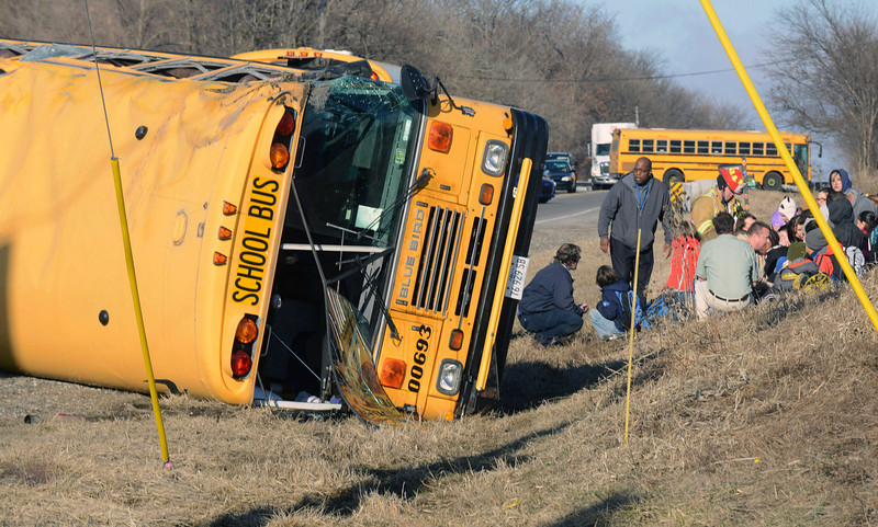 . Rescue personnel attend to children from Newport Elementary School after their school bus overturned Friday, April 5, 2015, near Wadsworth, Ill. There were about two dozen children on board. There was no immediate word on injuries. (AP Photo/Lake County News-Sun, Thomas Delany Jr.)
