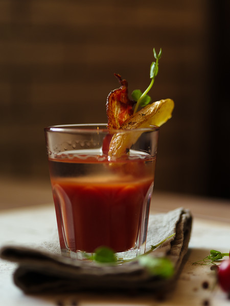 A glass of Bloody Mary with piece of bacon and potato on a top of a glass on a blurred background. A drink from organic cherry tomatoes, spicy peppercorns, vodka and green herbs on a white tablecloth.