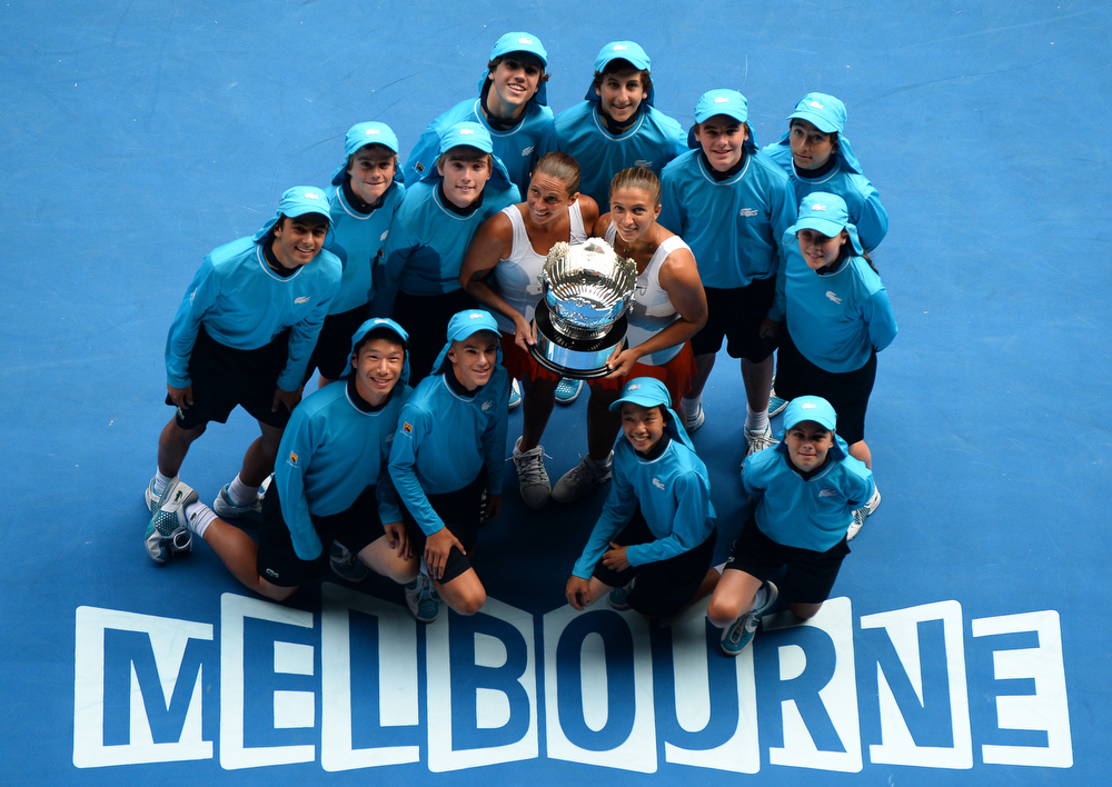 Description of . Sara Errani (R) and Roberta Vinci (L) of Italy pose with the trophy and ballboys as they celebrate after victory in their women's doubles final against Ashley Barty and Casey Dellacqua of Australia on day twelve of the Australian Open tennis tournament in Melbourne on January 25, 2013.   WILLIAM WEST/AFP/Getty Images