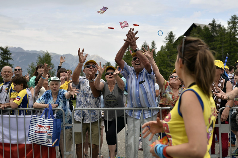 . Supporters receive Haribo sweets as they wait for riders near the finish line in Risoul, during the 177 km fourteenth stage of the 101st edition of the Tour de France cycling race on July 19, 2014 between Grenoble and Risoul, central eastern France.  (JEFF PACHOUD/AFP/Getty Images)