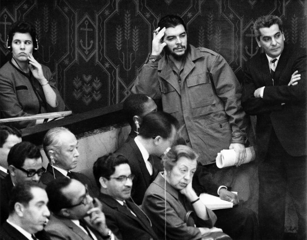 ". Cuba\'s Ernesto ""Che\"" Guevara, smoking a cigar and in uniform, leans against a wall in the spectator\'s gallery in the United Nations Security Council chamber, Dec. 14, 1964, as he listens to speech by U.S. ambassador to the U.N. Adlai Stevenson. Cuba has no seat in the Security Council. Guevara had to stand as there were no more chairs for spectators. (AP Photo/Harry Harris)"